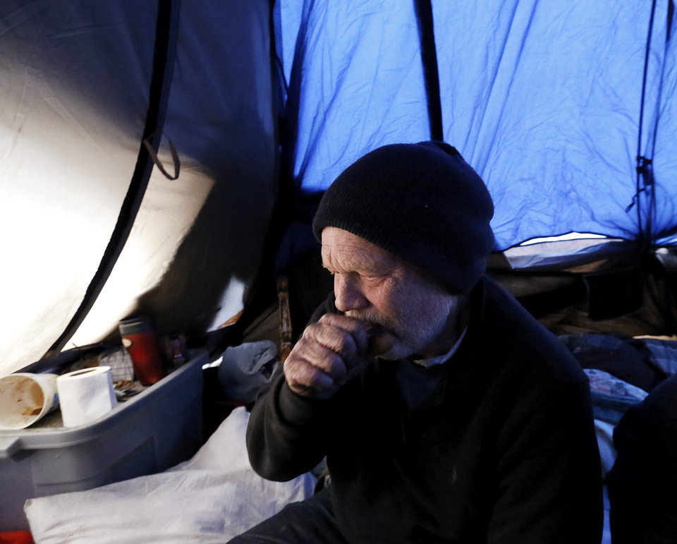 Photo - Jackson Poadger, 53, as he and three other adults are huddled inside his tent at a homeless encampment hidden by trees near Main Street and Villa. In preparation for this week's winter storms,  homeless shelters and organizations are ramping up efforts to house people during the coldest days the state has seen in several years. This includes actively going out to documented homeless camps and trying to convince people to accept a ride to an indoor shelter in Oklahoma City, but not everyone agrees to abandon their camps, some out of a fear that their material possessions will be stolen while they're gone.  Jonathon Roberts, with Be the Change, an Oklahoma City based non-profit that provides assistance to the homeless, gave Poadger and his friends extra blankets when he  checked on a number of encampments west of the downtown area Thursday afternoon, Dec. 5, 2013. Photo by Jim Beckel, The Oklahoman