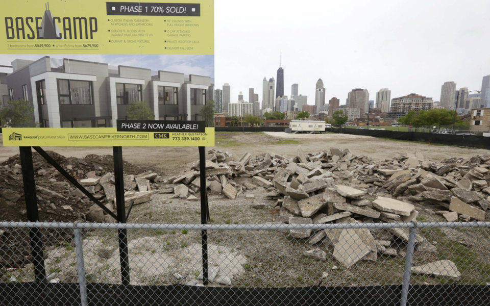 Photo - This May 14, 2014 photo shows signage advertising Basecamp River North, a housing development that recently broke ground in Chicago. Americans increasingly say they prefer to live near the centers of cities and towns, where commutes tend to be easier and culture, restaurants and entertainment close by. It marks a pronounced shift away from the yearning for open suburban space that drove U.S. home construction for decades. (AP Photo/M. Spencer Green)