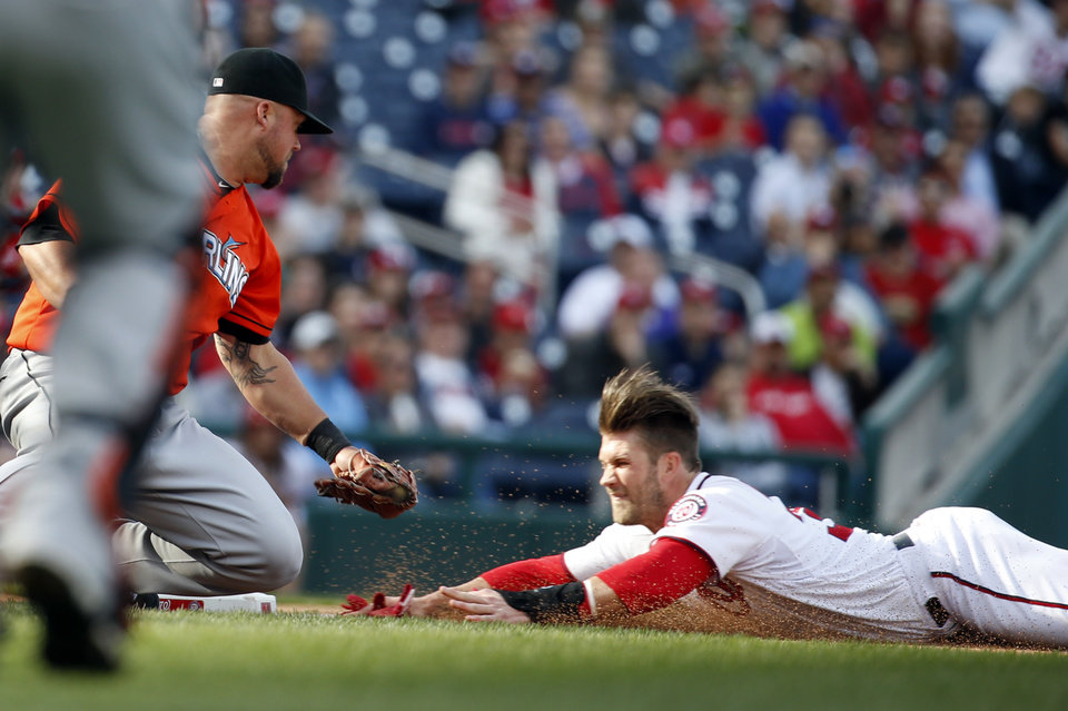 Photo - FILE - In this April 10, 2014, file photo, Washington Nationals' Bryce Harper slides safely into third as Miami Marlins third baseman Casey McGehee can't make the tag in time during the fourth inning of a baseball game at Nationals Park in Washington. Harper, Yasiel Puig of the Dodgers and Josh Hamilton of the Angels are among several stars who have gotten hurt sliding that way this year. (AP Photo/Alex Brandon, File)