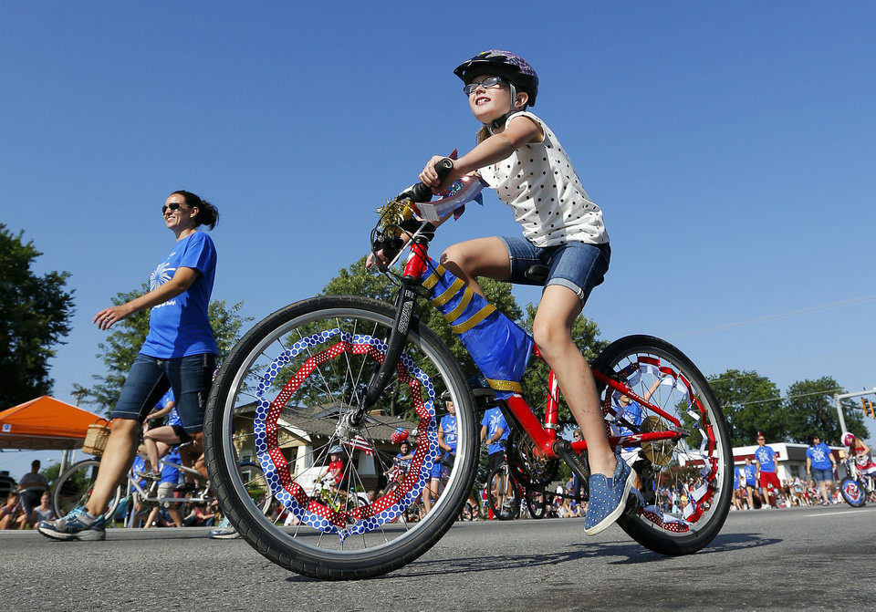 Photo - A girl on a decorated bike rides with others from the YMCA during the Edmond LibertyFest Parade in downtown Edmond, Okla., on Independence Day, Friday, July 4, 2014. Photo by Nate Billings, The Oklahoman