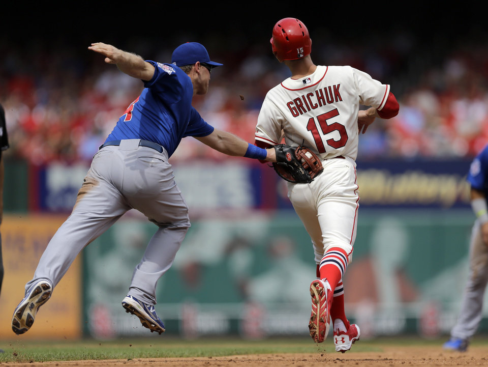 Photo - St. Louis Cardinals' Randal Grichuk, right, is tagged out by Chicago Cubs first baseman Chris Valaika after being caught in a run down between first and second during the third inning in the first baseball game of a doubleheader, Saturday, Aug. 30, 2014, in St. Louis. (AP Photo/Jeff Roberson)