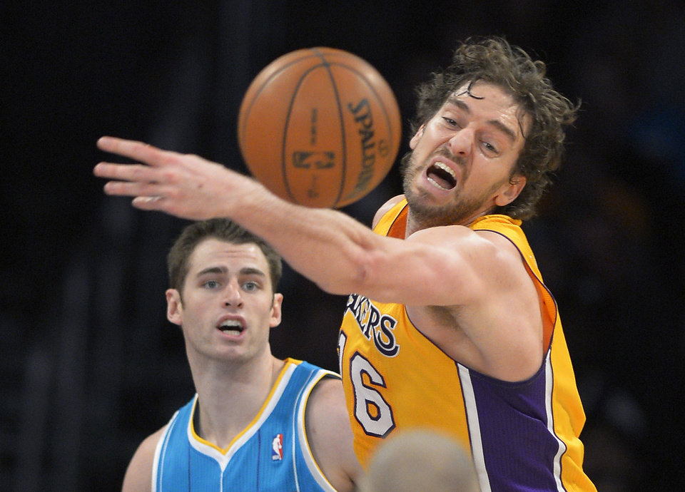 Los Angeles Lakers forward Pau Gasol, right, of Spain, reaches for a rebound as New Orleans Hornets forward Jason Smith looks on during the first half of an NBA basketball game, Tuesday, Jan. 29, 2013, in Los Angeles. (AP Photo/Mark J. Terrill)