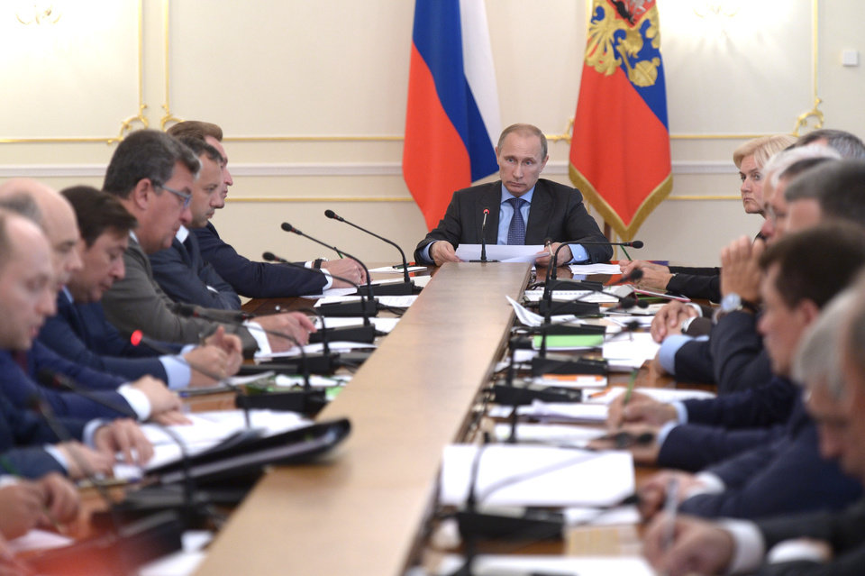 Photo - Russian President Vladimir Putin, background center, heads the Cabinet meeting in the Novo-Ogaryovo residence, outside Moscow, Russia, Wednesday, July 30, 2014. The meeting focused on measures to encourage Russian companies to pull their assets back from offshore. The United States and the European Union on Tuesday announced a raft of new sanctions against Russian companies and banks over Moscow's support for separatists in Ukraine. (AP Photo/RIA Novosti, Alexei Nikolsky, Presidential Press Service)