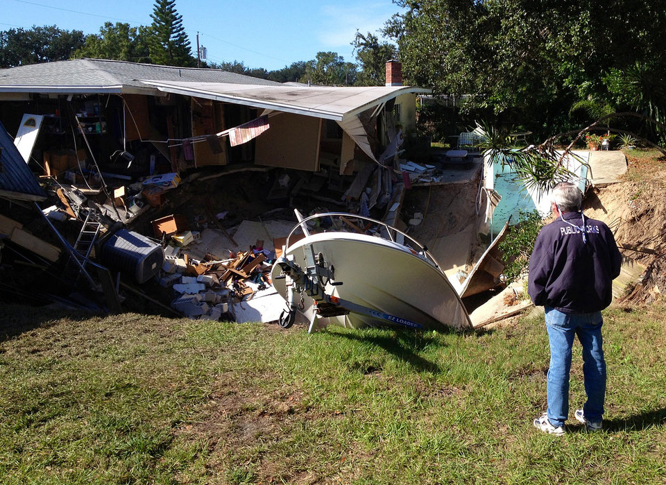 A man observes a sinkhole has swallowed parts of two houses in Dunedin, Fla. on Thursday, Nov. 14, 2013.   Dunedin Deputy Fire Chief Trip Barrs said the hole appeared to be about 12-feet wide when officials arrived on the scene. Residents of the neighboring houses also were evacuated as a precaution.  There are no reports of injuries. (AP Photo/The Tampa Tribune, Luke Johnson)  ST. PETERSBURG OUT; LAKELAND OUT; BRADENTON OUT; MAGS OUT; LOCAL TV OUT; WTSP CH 10 OUT; WFTS CH 28 OUT; WTVT CH 13 OUT; BAYNEWS 9 OUT; THE TAMPA BAY TIMES OUT; LAKELAND LEDGER OUT; BRADENTON HERALD OUT; SARASOTA HERALD-TRIBUNE OUT; WINTER HAVEN NEWS CHIEF OUT