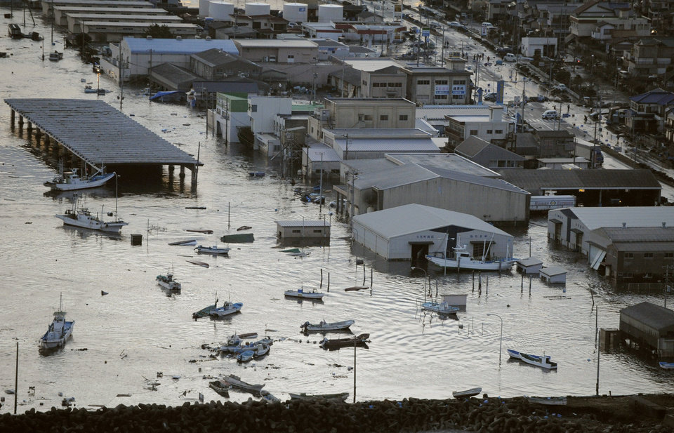 Photo - A port is submerged after a tsunami spawned by a powerful earthquake in Oarai town, Ibaraki prefecture (state), Japan, Friday, March 11, 2011. The powerful tsunami spawned by the largest earthquake in Japan's recorded history slammed the eastern coast Friday, sweeping away boats, cars, homes and people. (AP Photo/Kyodo News) JAPAN OUT, MANDATORY CREDIT, FOR COMMERCIAL USE ONLY IN NORTH AMERICA ORG XMIT: TOK808