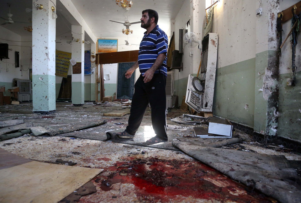 Photo - A man walks past blood stains on the floor of the Imam Ali mosque after a suicide bomb attack in New Baghdad, Iraq, Monday, Aug. 25, 2014. Iraqi officials say a wave of attacks targeting commercial areas in and outside Baghdad has killed and wounded scores of people. They say the deadliest of Monday's bombings was carried out by a suicide bomber who blew up himself among Shiite worshippers who were leaving Imam Ali mosque after noon prayers in the capital's eastern New Baghdad area, killing over a dozen people and wounding many others. (AP Photo/ Khalid Mohammed)