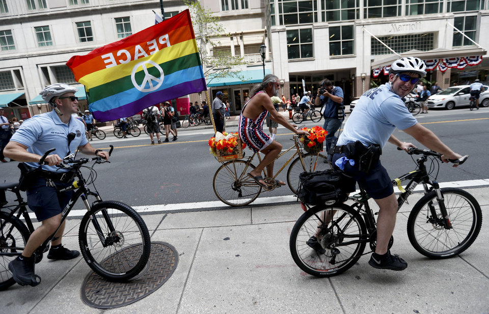 Photo - A pace protester rides past police officers on bikes, Sunday, July 24, 2016, in Philadelphia. The Democratic National Convention starts Monday in Philadelphia. (AP Photo/Alex Brandon)