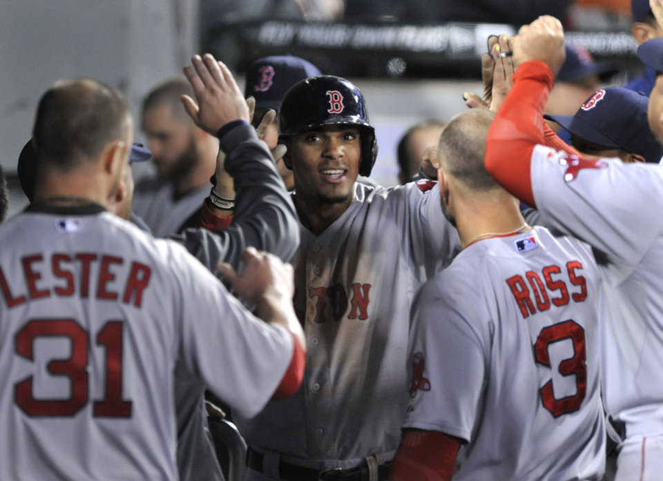 Photo - Boston Red Sox's Xander Bogaerts celebrates with teammates in the dugout after hitting a solo home run during the sixth inning of a baseball game against the Chicago White Sox in Chicago, Thursday, April 17, 2014. (AP Photo/Paul Beaty)