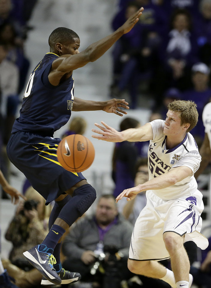 Photo - Kansas State's Will Spradling (55) passes around West Virginia's Eron Harris (10) during the first half of an NCAA college basketball game Saturday, Jan. 18, 2014, in Manhattan, Kan. (AP Photo/Charlie Riedel)