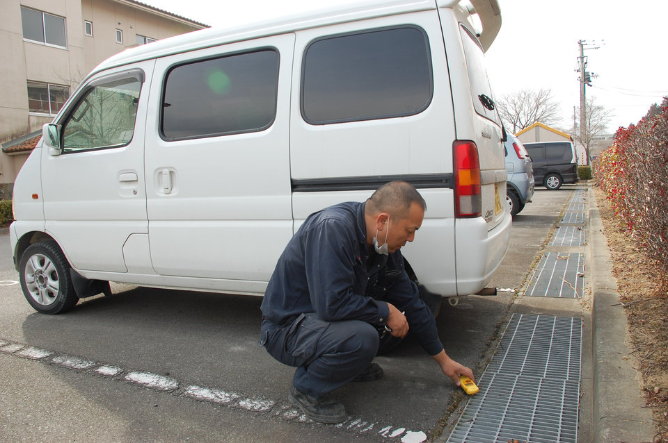 In this Friday, March 1, 2013 photo, truck driver Takahiro Ishitani checks radiation level in the parking lot of his apartment in Minami-Soma, Fukushima prefecture, Japan. Japan's radiation nightmare has turned Ishitani's life upside down, and the lively home he once shared with his wife and three sons into a cluttered bachelor pad, two years after an earthquake and tsunami caused meltdowns and explosions at the Fukushima Dai-ichi nuclear power plant that sent his family and many other residents fleeing. (AP Photo/Malcolm Foster)