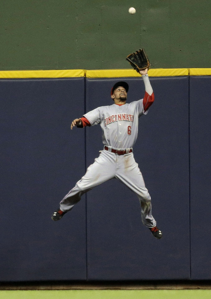 Photo - Cincinnati Reds' Billy Hamilton makes a leaping catch on a ball hit by Milwaukee Brewers' Ryan Braun during the sixth inning of a baseball game on Saturday, June 14, 2014, in Milwaukee. (AP Photo/Jeffrey Phelps)