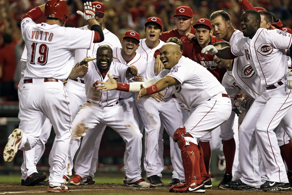 Photo - Cincinnati Reds' Joey Votto (19) is met at home plate after hitting a walkoff solo home run off Colorado Rockies relief pitcher Boone Logan in the ninth inning of a baseball game on Friday, May 9, 2014, in Cincinnati. Cincinnati won 4-3. (AP Photo/Al Behrman)