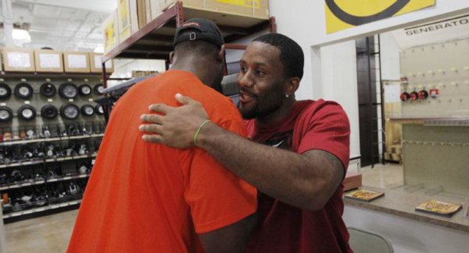 Photo - Dominique Franks, a former OU football player and current NFL player for Atlanta, right, greets Brandon Pettigrew, a former OSU football player and current NFL player for Detroit, during an autograph session at Northern Tool + Equipment, 1600 W I-240 Service Road, in Oklahoma City, Saturday, June 18, 2011. Franks signed autographs in the morning, while Pettigrew signed in the afternoon. Photo by Nate Billings, The Oklahoman ORG XMIT: KOD