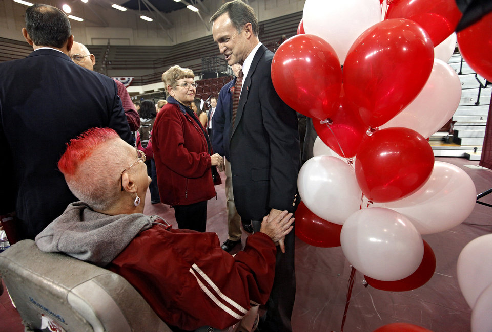 Photo - New University of Oklahoma men's basketball coach Lon Kruger speaks fan Carolyn Powell after he was introduced as the new University of Oklahoma men's basketball coach on Monday, April 4, 2011, in Norman, Okla.