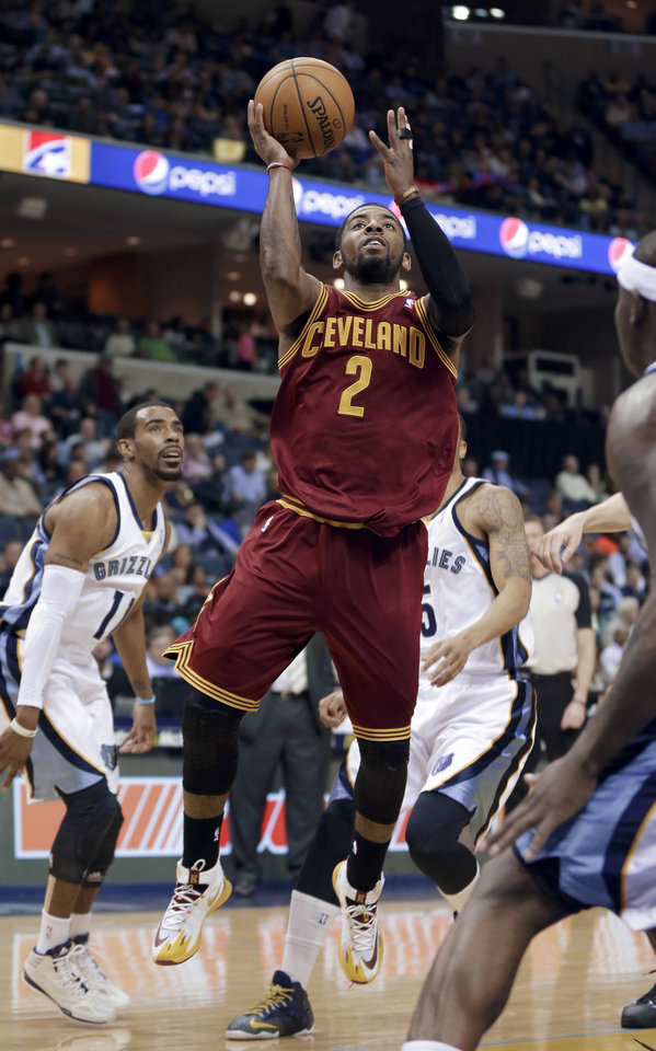 Photo - Cleveland Cavaliers' Kyrie Irving (2) goes to the basket in front of Memphis Grizzlies' Mike Conley, left, and Courtney Lee during the first half of an NBA basketball game in Memphis, Tenn., Saturday, March 1, 2014. (AP Photo/Danny Johnston)