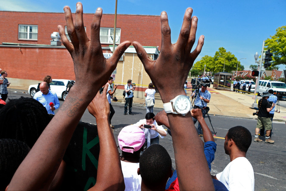 Photo - Members of a crowd gathered after a police-involved shooting, raise hands chanting