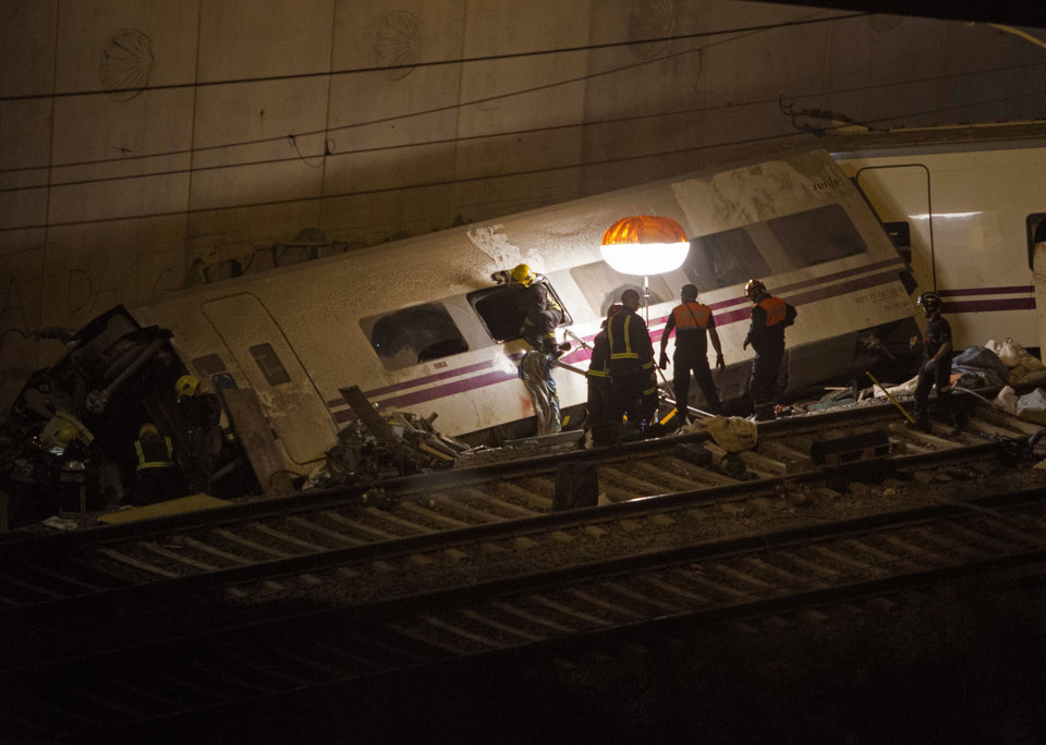 Photo - Emergency personnel conduct rescue operation at the site of a train derailed in Santiago de Compostela, Spain, on Thursday, July 25, 2013.  A passenger train derailed Wednesday night on a curvy stretch of track in northwestern Spain, killing at least 40 people caught inside toppled cars and injuring at least 140 in the country's worst rail accident in decades, officials said. (AP Photo/ Lalo Villar)