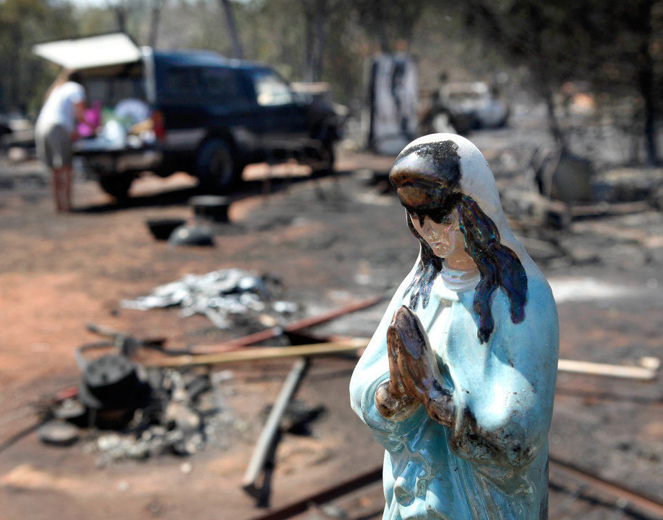 Photo - A religious statue of a praying Madonna was recovered from the charred rubble of Lori Turner's home at 6000 NE 63 after wildfires ravaged land and property that stretched from NE 50 on the south to Hefner Road on the north.  The fire extended from Sooner Road to Midwest Blvd.   The statue was on a cart with other glassware and knicknacks she had recovered Wednesday morning. Turner can be seen in background loading items into her truck.  Photo taken Wednesday, Aug. 31, 2011. Photo by Jim Beckel, The Oklahoman