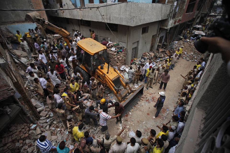 Photo - EDS: GRAPHIC CONTENT - Rescue workers carry the body of a victim out of the debris of a building that collapsed in New Delhi, India, Saturday, June 28, 2014. A dilapidated building collapsed in the Indian capital on Saturday, killing at least seven people as rescuers searched for others believed to be trapped. (AP Photo/Altaf Qadri)
