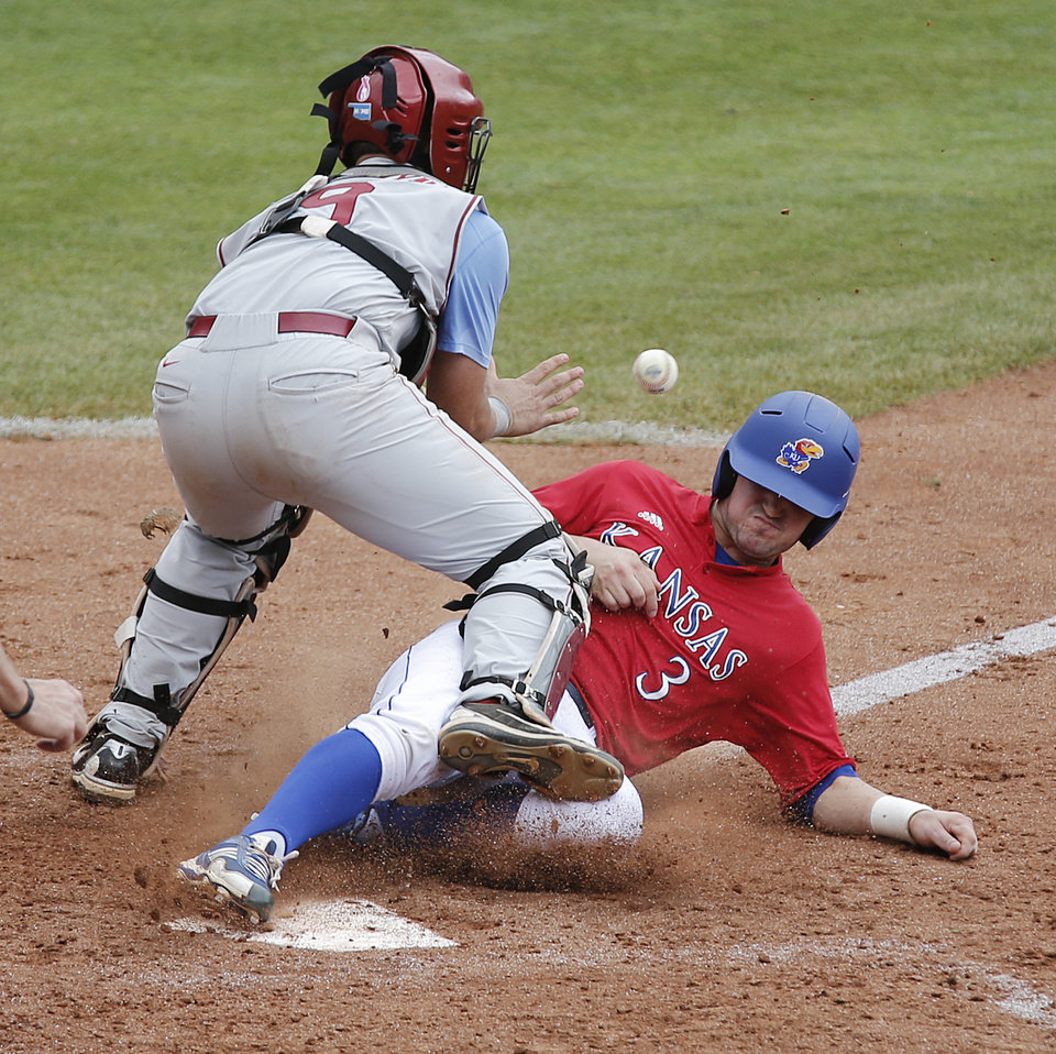 Kansas' Dakota Smith (3) slides into home plate against Oklahoma's Anthony Hermelyn (9) in the Big 12 Championship baseball game between the University of Kansas Jayhawks (KU) and the University of Oklahoma Sooners (OU) at the Chickasaw Bircktown Ballpark on Sunday, May 26, 2013 in Oklahoma City, Okla.  Photo by Chris Landsberger, The Oklahoman