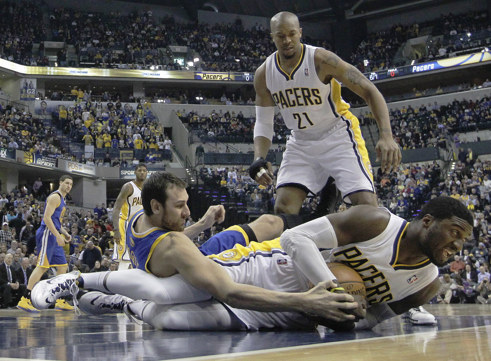 Photo - Indiana Pacers' Roy Hibbert (55) and Golden State Warriors' Andrew Bogut (12) battle for a loose ball as David West (21) watches during the first half of an NBA basketball game Tuesday, March 4, 2014, in Indianapolis. (AP Photo/Darron Cummings)