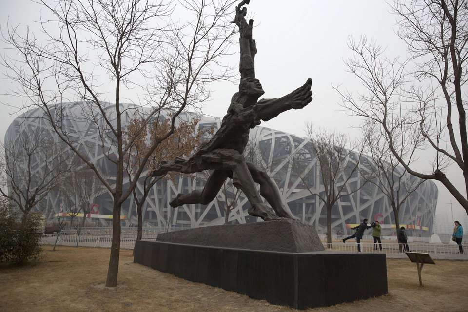 Photo - In this picture taken, Sunday, Feb. 23, 2014, a tourist poses near giant sculptures near the iconic Bird's Nest National Stadium in Beijing, China. The National Stadium, nicknamed the Bird's Nest because of its lattice design, has become a key Beijing landmark and a favored backdrop for visitors' snapshots. But few tourists are willing to pay more than $8 to tour the facility as enthusiasm for the 2008 Games fades, and the venue has struggled to fill its space with events. Beijing, which spent more than $2 billion to build 31 venues for the 2008 Summer Games, is reaping some income and tourism benefits from two flagship venues, though many sites need government subsidies to meet hefty operation and maintenance costs. (AP Photo/Ng Han Guan)