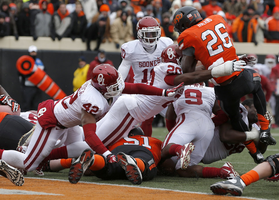 Photo - The Oklahoma defense, including Dominique Alexander (42) and Frank Shannon (20) stop Oklahoma State's Desmond Roland (26) on a fourth down at the goal line during the Bedlam college football game between the Oklahoma State University Cowboys (OSU) and the University of Oklahoma Sooners (OU) at Boone Pickens Stadium in Stillwater, Okla., Saturday, Dec. 7, 2013. Photo by Bryan Terry, The Oklahoman