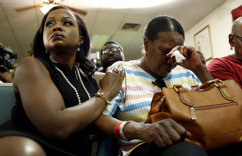 Photo - Phaedra Parks, left, comforts Desuirea Harris, the grandmother of Michael Brown, during a news conference Monday, Aug. 11, 2014, in Jennings, Mo. Michael Brown, 18, was shot and killed in a confrontation with police in the St. Louis suburb of Ferguson, Mo, on Saturday, Aug. 9, 2014.(AP Photo/Jeff Roberson)