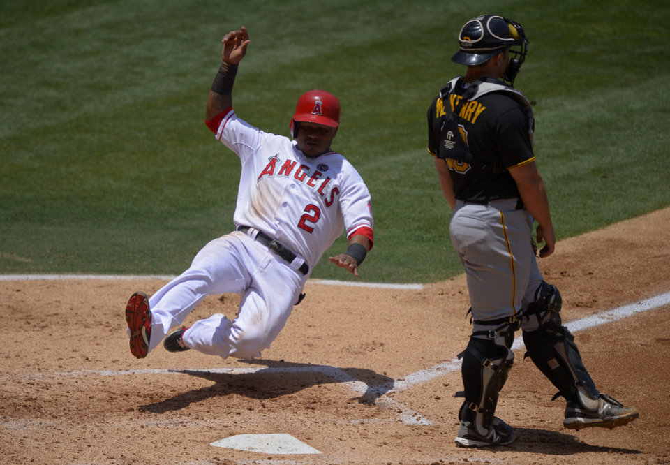 Photo - Los Angeles Angels' Erick Aybar, left, scores on a single by J.B. Shuck as Pittsburgh Pirates catcher Michael McKenry looks on during the second inning of their baseball game on Sunday, June 23, 2013, in Anaheim, Calif.  (AP Photo/Mark J. Terrill)
