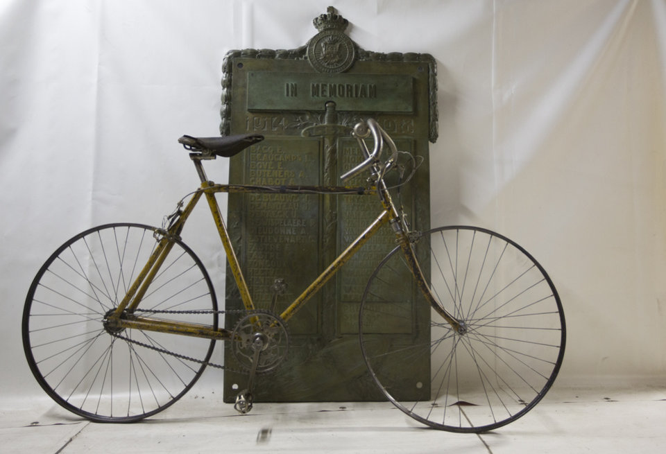 Photo - In this June 17, 2014, a bicycle from 1912 stands against a plaque listing the names of Belgian cyclists who died during World War I at the WielerMuseum in Roeselare, Belgium. Three former winners of the Tour de France; Octave Lapize, Francois Faber and Lucien Petit-Breton all died fighting in World War I. Many more, both Belgian, French, German and Italian died serving their countries during the four years of war. (AP Photo/Virginia Mayo)