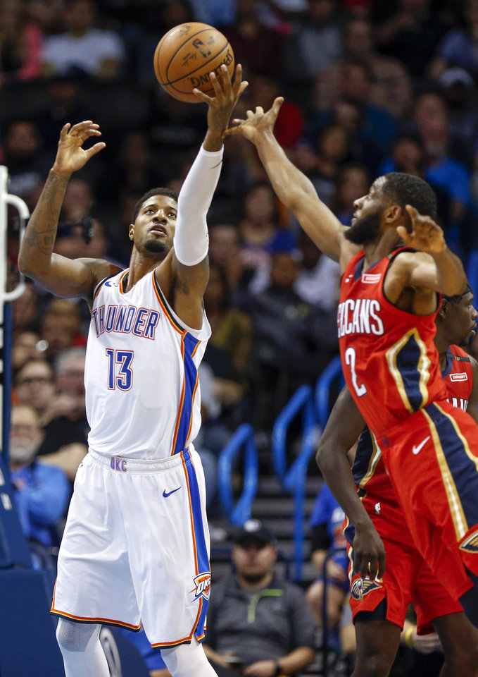 Photo - Oklahoma City's Paul George (13) grabs a rebound next to New Orleans' Ian Clark (2) during an NBA basketball game between the Oklahoma City Thunder and the New Orleans Pelicans at Chesapeake Energy Arena in Oklahoma City, Monday, Nov. 5, 2018. Oklahoma City won 122-116. Photo by Nate Billings, The Oklahoman