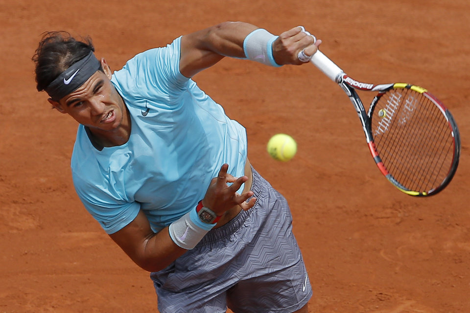 Photo - Spain's Rafael Nadal serves the ball during the fourth round match of the French Open tennis tournament against Serbia's Dusan Lajovic at the Roland Garros stadium, in Paris, France, Monday, June 2, 2014. (AP Photo/Michel Spingler)