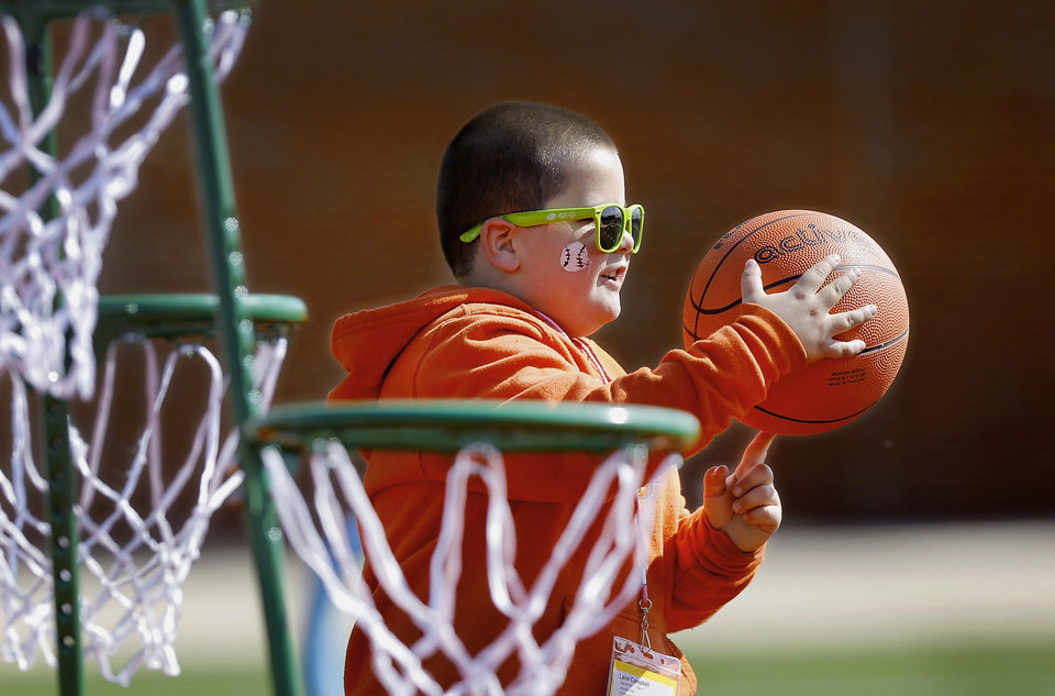 Photo - Lane Campbell, 6, of Mooreland, tries to spin a basketball  on his finger before he shoots it into one of several nets on a stand in the 'Stars of the Future' area north of Boone Pickens Stadium on the campus of Oklahoma State University on Thursday, May 15, 2014.  Campbell's mother said her son is autistic. Special Olympics athletes numbering in the thousands are competing in various events today and tomorrow  in Stillwater as the organization's 45th Annual Summer Games are held in Oklahoma this week.  Officials say more than 4,600 Special Olympics Oklahoma athletes have registered to compete this year, and thousands of volunteers are assisting during the three days of competitions.   This is the 31st year the summer games has been centered at Oklahoma State University.  Special Olympics is the world's largest sports organization for children and adults with intellectual disabilities, providing year-round training and competitions to more than 4.2 million athletes in 170 countries, according to their web site. Photo by Jim Beckel, The Oklahoman