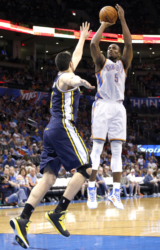 Photo - Oklahoma City 's Serge Ibaka (9) shoots as Enes Kanter (0) during the NBA game between the Oklahoma City Thunder and the Utah Jazz at the Chesapeake Energy Arena, Sunday, March 30, 2014, in Oklahoma City. Photo by Sarah Phipps, The Oklahoman