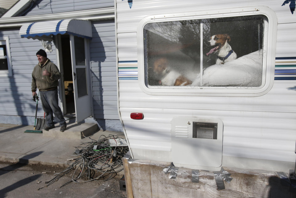 The Colombo's dogs, Jake and Jet, look out the window of the mobile home where they are living in the Broad Channel section of Queens, New York, Thursday, Jan. 3, 2013.  The Colombos are living in a mobile home while working on their house, which was damaged by Superstorm Sandy. Many home and business owners flooded out by Hurricane Sandy could get insurance payouts soon through congressional action expected Friday, Jan. 4 on a $9.7 billion bill to replenish the National Flood Insurance Program. The Federal Emergency Management Agency, which runs the program, warned that it will run out of money next week if Congress doesn�t give it additional borrowing authority to pay out claims. (AP Photo/Seth Wenig)