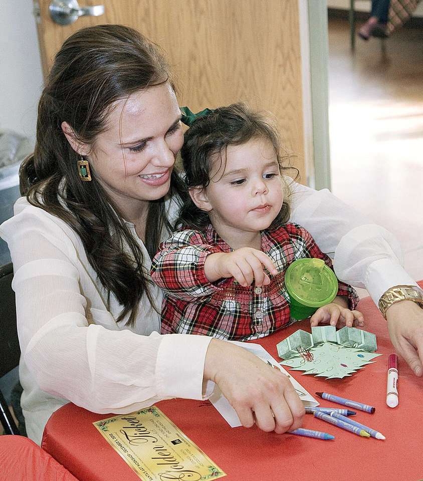 Right: Genevieve Darwiche helps her daughter, Eleanor, color a holiday pop-up card during the Santa�s Art Workshop at the Edmond Fine Arts Institute.