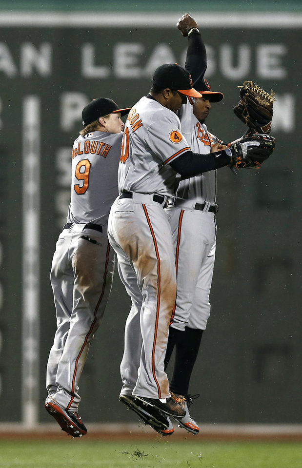 From left to right, Baltimore Orioles' Nate McLouth, Chris Dickerson and Adam Jones celebrate after their 3-2 win against the Boston Red Sox in a baseball game at Fenway Park in Boston, Thursday, April 11, 2013. (AP Photo/Winslow Townson)