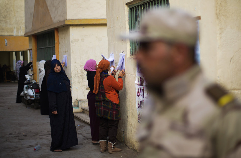 Photo - An Egyptian army soldier stands guards the entrance of a polling station as women search for their names on a polling list before casting their votes in the country's constitutional referendum in Cairo, Egypt, Tuesday, Jan. 14, 2014. Egyptians have started voting on a draft for their country's new constitution that represents a key milestone in a military-backed roadmap put in place after President Mohammed Morsi was overthrown in a popularly backed coup last July.(AP Photo/Khalil Hamra)