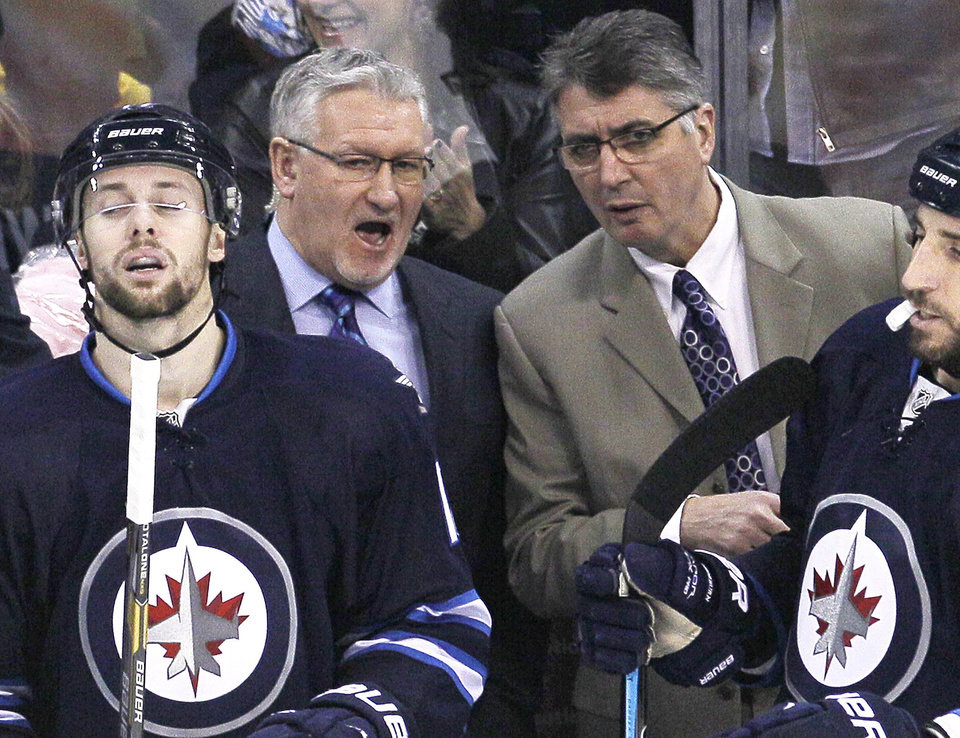 Photo - Winnipeg Jets head coach Claude Noel, right, and assistant coach Perry Pearn talk during first period NHL action against the Columbus Blue Jackets in Winnipeg, Manitoba, on Saturday, Jan. 11, 2014. Noel is out as coach of the Jets, replaced by Paul Maurice. Pearn was also fired.(AP Photo/The Canadian Press, John Woods)
