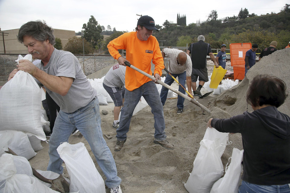 Photo - Volunteers, from left, Steve Hamilton, Thomas Lubboch and Becky Chen help fill sandbags before an expected storm Wednesday Feb. 26, 2014 in Glendora, Calif. Much-needed rain fell in Northern California on Wednesday at the outset of what the parched state hopes is the start to a one-two punch of stormy weather with a half inch of rain predicted.  (AP Photo/Nick Ut )