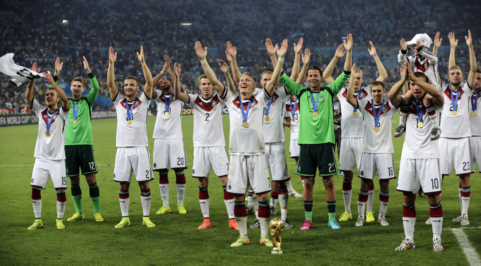 Photo - German players celebrate with the trophy after the World Cup final soccer match between Germany and Argentina at the Maracana Stadium in Rio de Janeiro, Brazil, Sunday, July 13, 2014. Germany won the match 1-0. (AP Photo/Matthias Schrader)