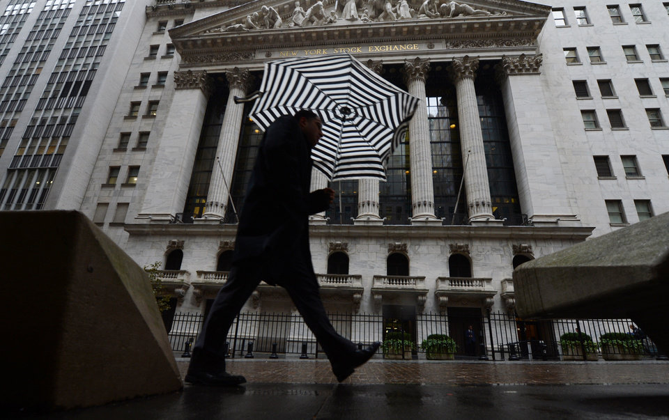 Photo - A pedestrian walks past the New York Stock Exchange the day after Pres. Barack Obama was re-elected, Wednesday, Nov. 7, 2012 in New York. A new storm that threatened to complicate Hurricane Sandy cleanup efforts on Wednesday now looks like it will be weaker than expected.  Winds could still gust to 50 mph in New York and New Jersey Wednesday afternoon and evening. (AP Photo/Henny Ray Abrams) ORG XMIT: NYHA112