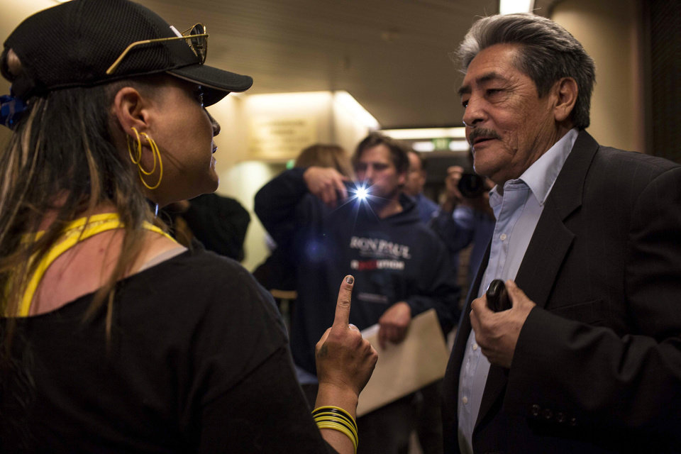 Photo - Jennifer Otte argues with activist Andres Valdez prior to a city council meeting in Albuquerque, N.M., Thursday, May 8, 2014. The Albuquerque City Council gathered Thursday under new rules and heightened security designed to avoid an angry confrontation like the one that broke out earlier in the week amid community outrage over a spate of deadly police shootings.  (AP Photo/Juan Antonio Labreche)