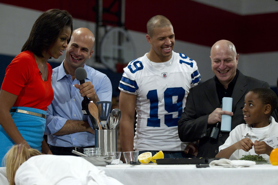"FILE - In this Feb. 10, 2012 file photo, from left, First lady Michelle Obama, Sam Kass assistant White House chef and Food initiative Coordinator, Dallas Cowboys football wide receiver Miles Austin, ""Top Chef"" Head Judge Tom Colicchio and Trey Payton of Nancy Moseley Elementary School participate in a Let's Move event at Kleberg Rylie Recreation Center in Dallas. Recent changes put in place by the food industry are in response to the campaign against childhood obesity that Obama began waging three years ago. (AP Photo/Carolyn Kaster, File)"