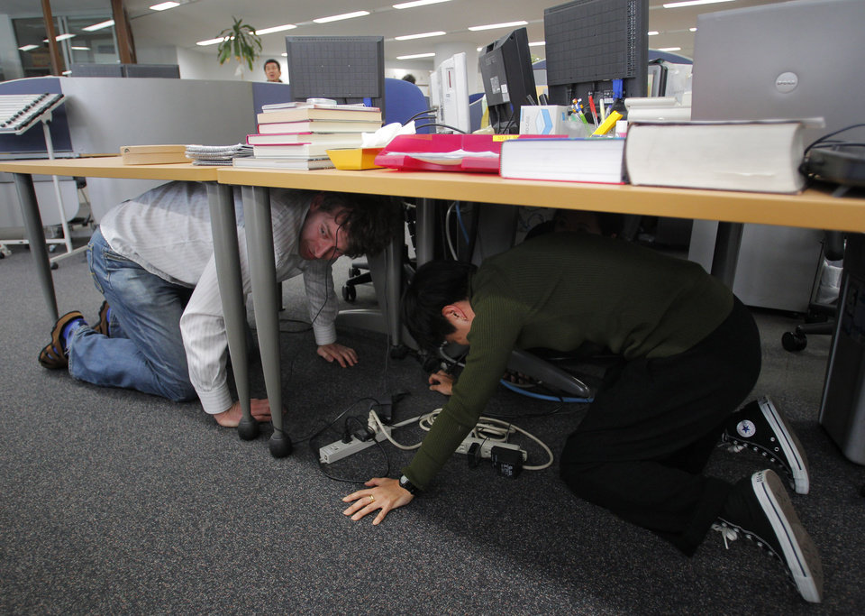 Photo - Reporters at the Associated Press Tokyo Bureau in Tokyo take shelter under a table while a strong earthquake strikes eastern Japan Friday afternoon, March 11, 2011. (AP Photo/Itsuo Inouye) ORG XMIT: XITS101