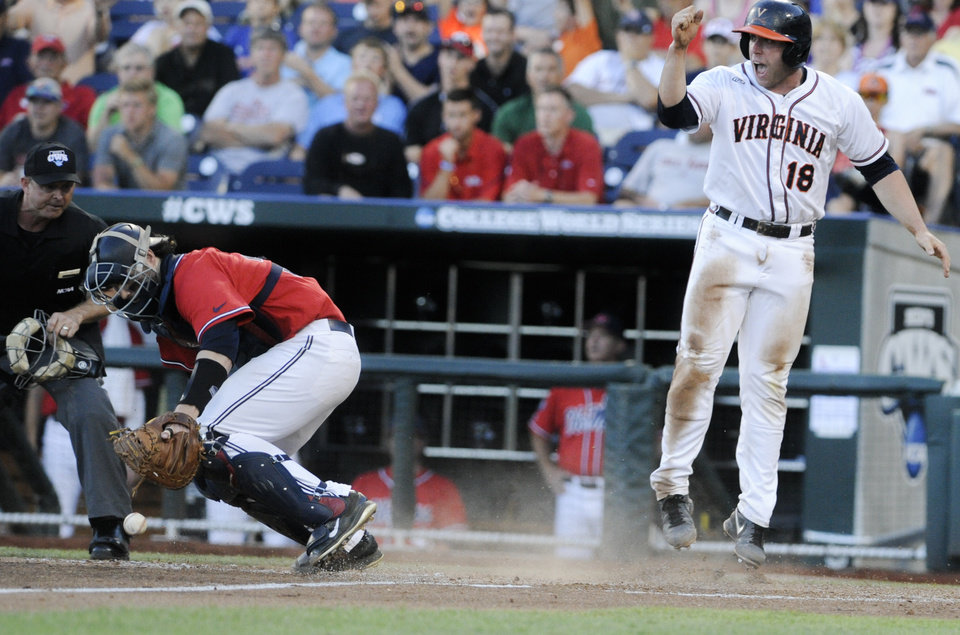 Photo - Virginia's Nate Irving, right, celebrates after scoring on a single by Joe McCarthy, as Mississippi catcher Will Allen goes after the ball, in the fifth inning of an NCAA baseball College World Series game in Omaha, Neb., Sunday, June 15, 2014.. (AP Photo/Eric Francis)