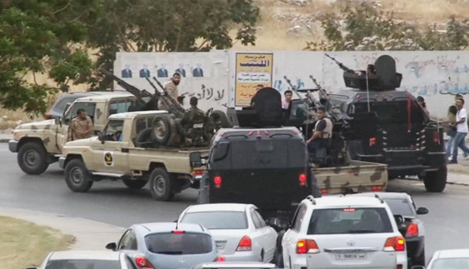 Photo - In this image made from video provided by the Libyan national army via AP Television, vehicles with heavy artillery of the Tripoli joint security forces move closer to the parliament building after troops of Gen. Khalifa Hifter targeted Islamist lawmakers and officials at the parliament in Tripoli, Libya, Sunday, May 18, 2014. Forces loyal to a rogue Libyan general attacked the country's parliament Sunday, expanding his eastern offensive against Islamists into the heart of the country's capital. (AP Photo/Libyan national army)