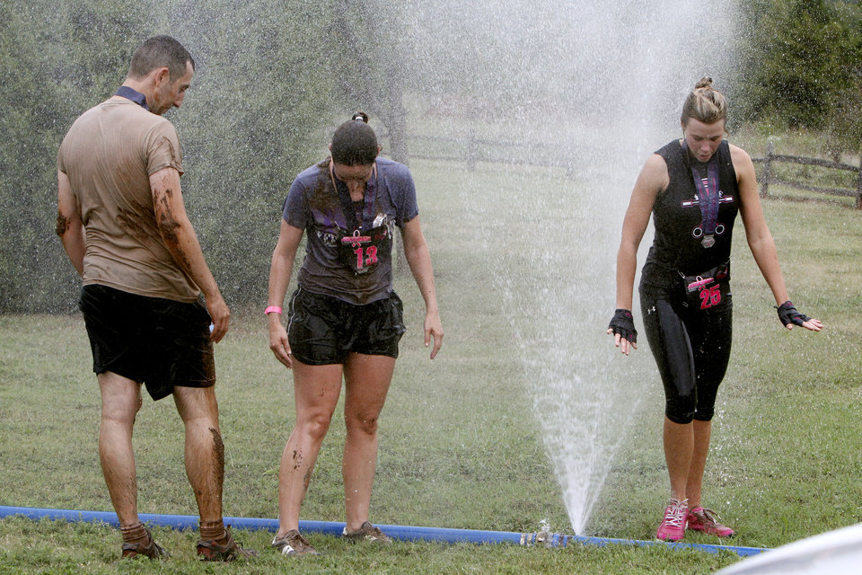 David Leibovich, right, Anna Christensen, and Michelle Goodnight rinse off after the Juggernaut mud run at Mitch Park, in Edmond, OK, Saturday, September 29, 2012. The Juggernaut is part of a national mud run series to raise money for Susan G. Komen for the Cure. By Paul Hellstern, The Oklahoman