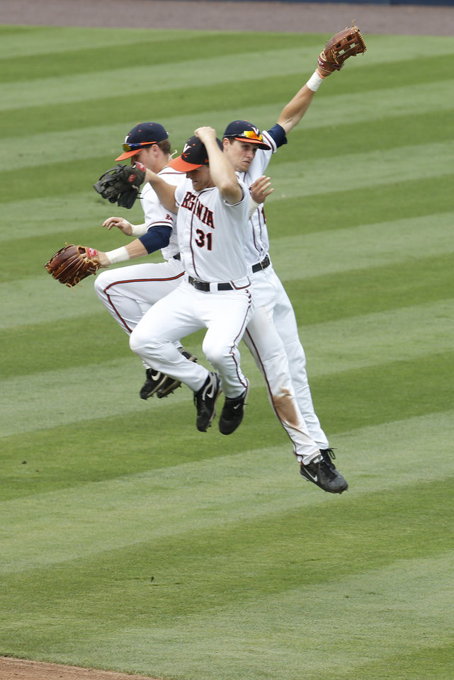 Photo - Virginia outfielders Derek Fisher, left, Joe McCarthy (31) and Brandon Downes (10) celebrate after Virginia's 10-1 win over Bucknell in an NCAA college baseball tournament regional game in Charlottesville, Va., Friday, May 30, 2014. (AP Photo/Steve Helber)