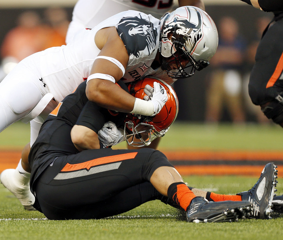 Photo - Oklahoma State's Daxx Garman (12) is sacked by Texas Tech's Pete Robertson (10) during a college football game between the Oklahoma State Cowboys (OSU) and the Texas Tech Red Raiders at Boone Pickens Stadium in Stillwater, Okla., Thursday, Sept. 25, 2014. Photo by Nate Billings, The Oklahoman